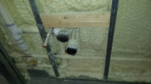 Foam insulation in the wall around a plumbing rough-in.