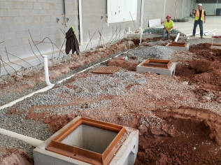 Upper Level wash bay underslab plumbing rough-in underway