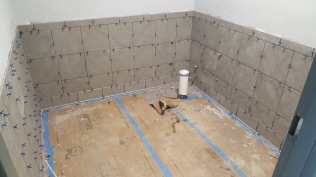 Ceramic wall and floor tile underway, ready for grout